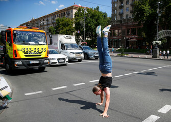 A man walks on his hands as he crosses a street in Kyiv