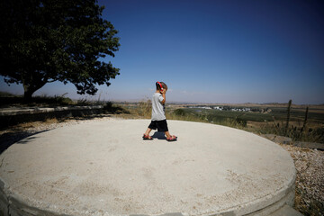 An Israeli boy uses headphones as he walks at a look-out point in the Israeli-controlled Golan Heights near the Israel-Syria frontier