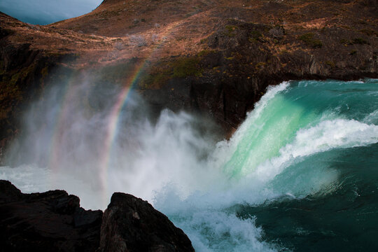 Scenic view of rainbow over waterfall flowing through rocks