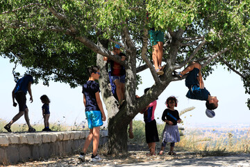 Israeli tourists play around as they visit a look-out point in the Israeli-controlled Golan Heights near the Israel-Syria frontier