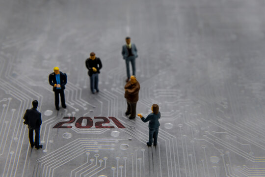 Miniature figurines posed as business people in a meeting over abstract futuristic circuit board with text year 2021