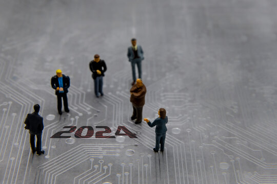 Miniature figurines posed as business people in a meeting over abstract futuristic circuit board with text year 2024