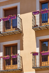 Stylish facade with traditional balconies and purple pots. Brihuega, Spain
