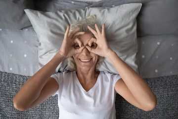 Top view grey haired elderly woman lying on pillow in bed smile look at camera through binoculars...