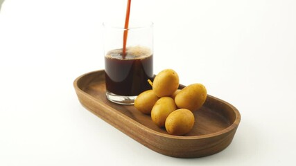 Fototapete - Pour dried date juice into a glass with bunch of freshly harvested date in wooden tray on white background.