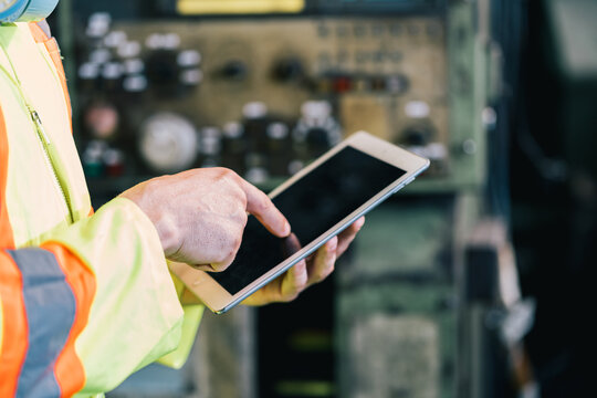 Closeup hand worker in protective safety jumpsuit uniform with yellow hardhat and using tablet at factory.Metal working industry concept professional engineer manufacturing