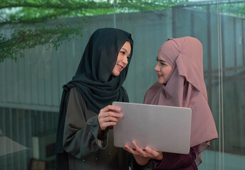Two beautiful Muslim ladies holding laptop in hand,and smile with happy feeling after success deal,business time