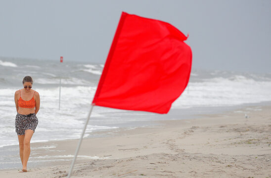 A storm warning flag flies as a woman walks along the surging surf on the beach ahead of Tropical Storm Isaias in the Rockaway area of Queens in New York
