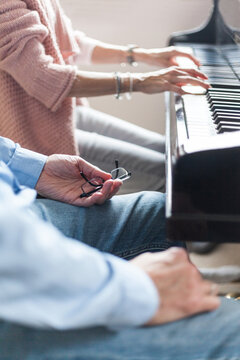 Piano teacher and music student together in front of the piano to learn acoustics new experience make late beginners music lessons classical hobby stress reduction education specialist music school