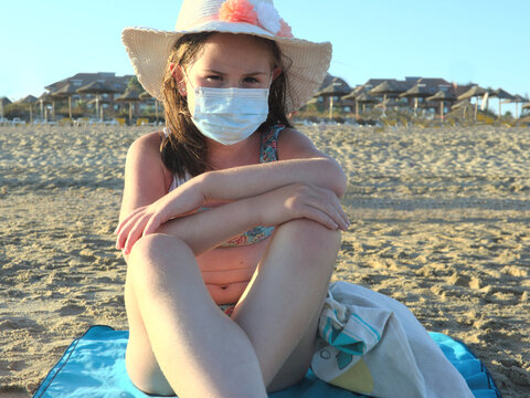 Girl in hat wearing surgical face mask at beach. New normality in covid-19 pandemic.