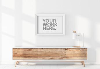 White Poster Frame Mockup Hanging on Wall Above Bureau