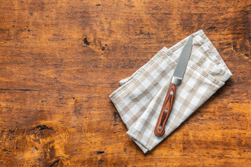 Kitchen knife on checkered napkin.