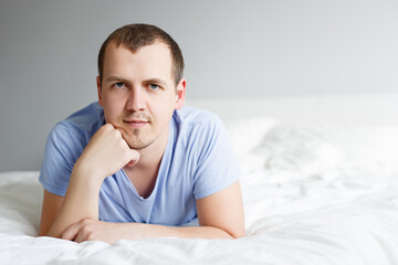 handsome man in pajamas lying on bed at home