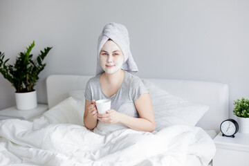 good morning and skin care concept - woman with facial mask sitting in bed and drinking coffee