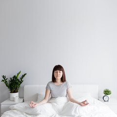 happy woman sitting on bed in yoga pose at home, copy space over white wall