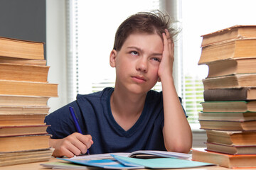 Portrait of upset schoolboy looking at textbook with homework