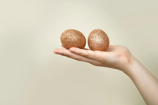 Minimalistic shot of women's hands holding golden eggs in front of a wall