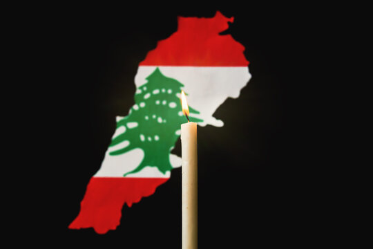 One light candle burning brightly and lebanon map with flag in the black background grunge sad style