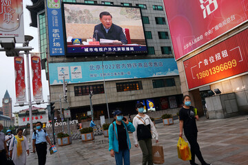 People hold shopping bags as they walk under a giant screen showing a news footage of Chinese President Xi Jinping, at a shopping area in Beijing