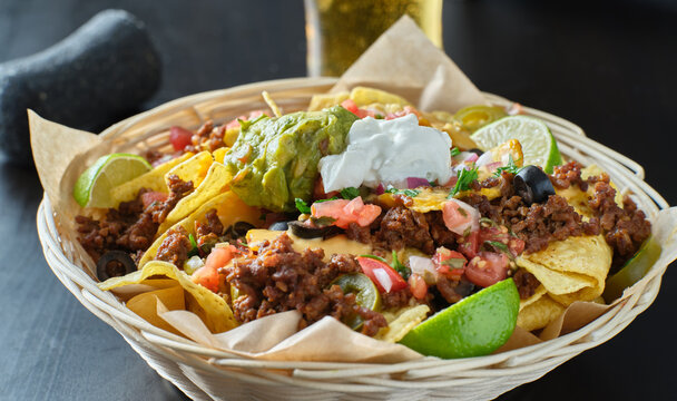 basket of load nachos with beef and cheese