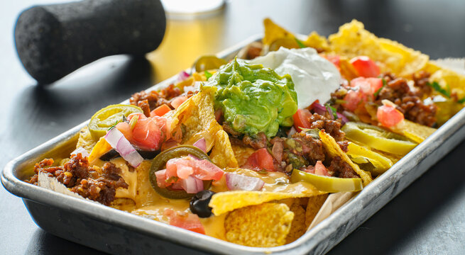 tray of loaded mexican nachos with beef and queso cheese