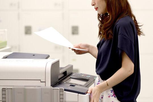 プリンターの前で書類を持つ女性