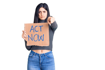 Young beautiful girl holding act now cardboard banner pointing with finger to the camera and to...