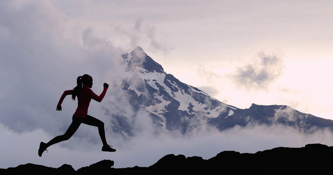 Running woman athlete sport concept. Trail runner exercising in mountain summit background. Female runner on run training outdoors living active fit lifestyle. Silhouette at sunset.