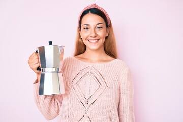 Young brunette woman holding italian coffee maker looking positive and happy standing and smiling with a confident smile showing teeth