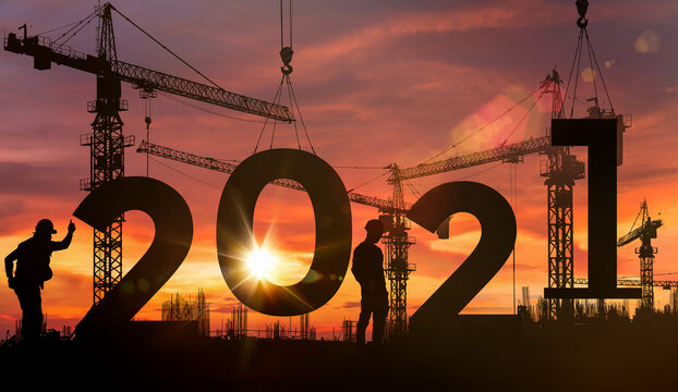Cranes building construction 2021 year sign,Silhouette staff works as a team to prepare to welcome the new year 2021