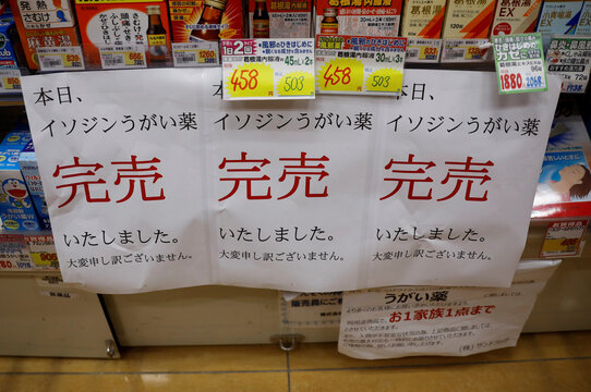 Banners notifying sold-out of gargling medicine are displayed at empty shelves at a drugstore in Tokyo