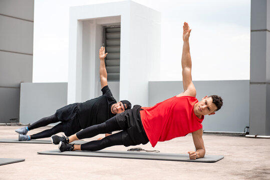 Group of athletic men doing side plank workout exercise outdoors on rooftop floor