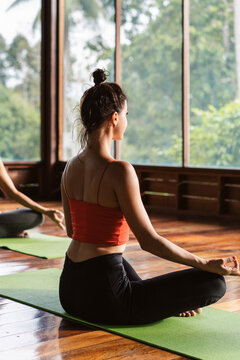 Young female meditating during yoga lesson