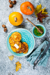 Pumpkin pancakes on rustic stone background, top view