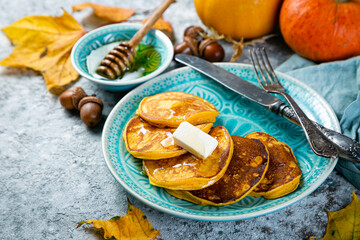 Pumpkin pancakes on rustic stone background, copy space