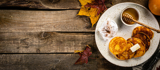 Pumpkin pancakes on rustic wood background, top view