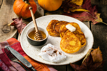 Pumpkin pancakes on rustic wood background, copy space