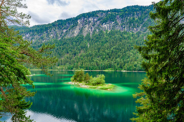 Small islands with pine-trees in the middle of Eibsee lake with Zugspitze mountain. Beautiful landscape scenery with paradise beach and clear blue water in German Alps, Bavaria, Germany, Europe.