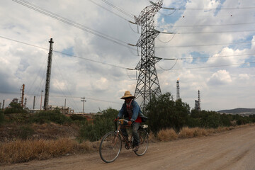 A man rides a bike on a road near high-voltage transmission lines near the Tula power plant owned by state-owned power company Comision Federal de Electricidad, or CFE, in Tula de Allende