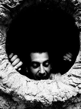 Smiling Man Looking Through Cave
