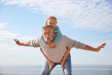 Little girl playing with grandfather on sea beach
