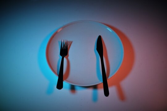 Directly Above Shot Of White Dish Folk Anf Knife On Plate Against Blue Wall