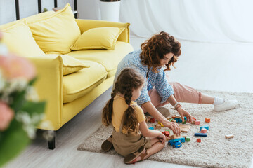 selective focus of young nanny and kid sitting on floor and playing with multicolored blocks