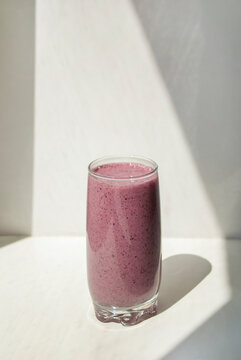 Blueberry smoothie in glass on light background with long shadows. Milk Shakes