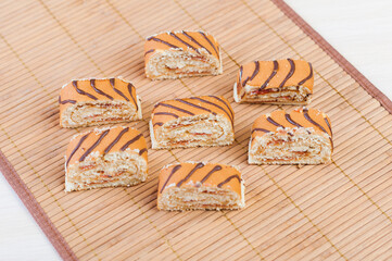 Delicious sliced roll with chocolate wavy stripes on a bamboo napkin.