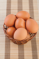 Several eggs lying in a wicker basket on striped bamboo tablecloth.