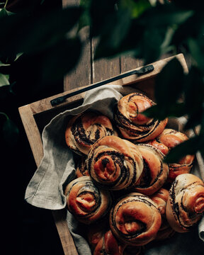 baked buns with poppy seeds on a brown wooden board