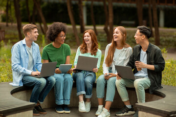Diverse Multicultural Students Studying Outdoors With Different Electronic Devices, Sitting On Bench