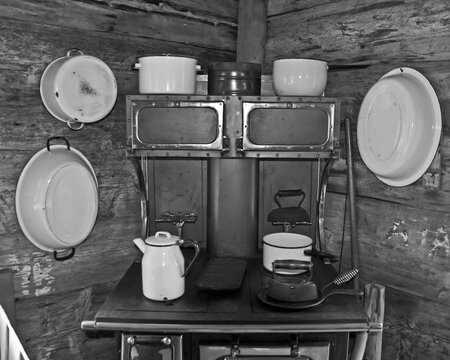 Vintage kitchen with a wood stove, wash basins on the log cabin walls, and more home related pioneer era objects.