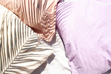 Three pillows white, lavender and peach on the bed. Contrasting shadows with palm leaves